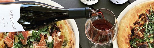 photo of pizza and bottle of red wine being poured